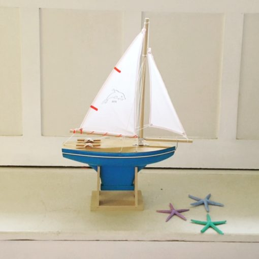 The boat has led-free paint and it is made out of beech wood grown in sustainable forests in France. It has a dolphin motif hand-stamped on the sail.